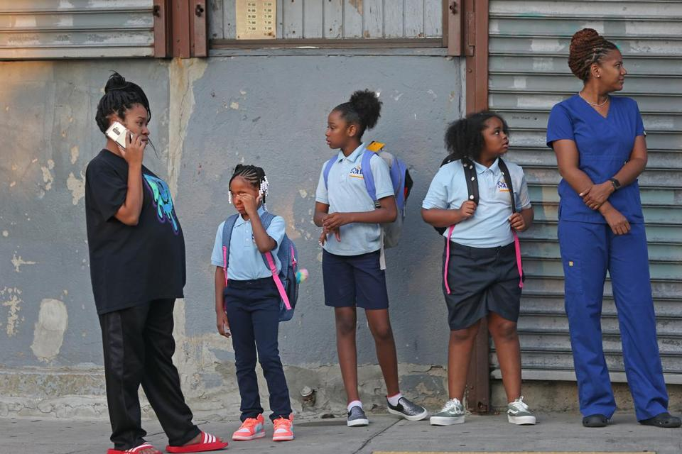 Third-grade student Heaven Jones rubbed her eyes while she waited for the bus with her mother Diamond Jones (left) at Geneva Avenue and Westville Street with other students and parents.